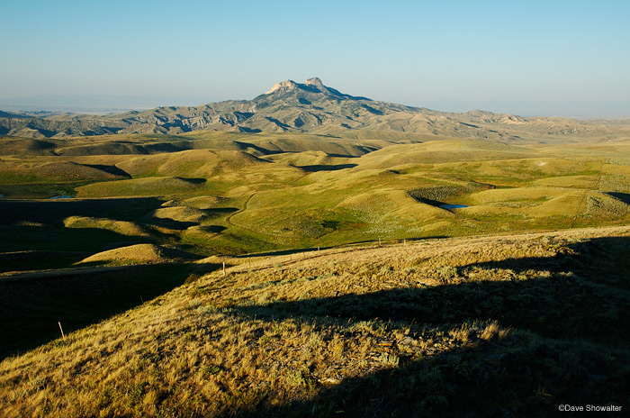 Evening shadows and rolling sagebrush surrounding Heart Mountain, an icon of the A-B Front. The Nature Conservancy's Heart Mountain...