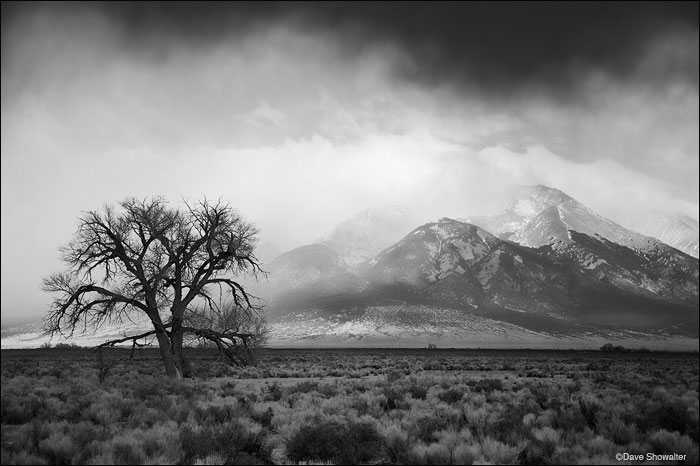 A spring storm passes the Blanca group in the southern Sangre De Cristo Range as sun lights the base of the mountains....