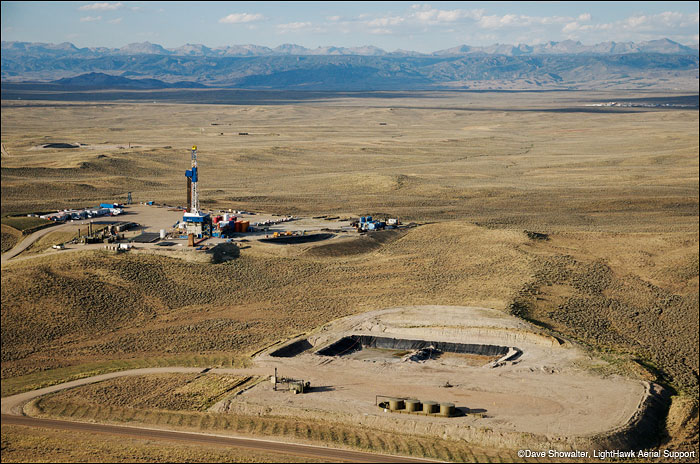 High density gas drilling operations in the Jonah Field contrast with the rugged Wind River Range.