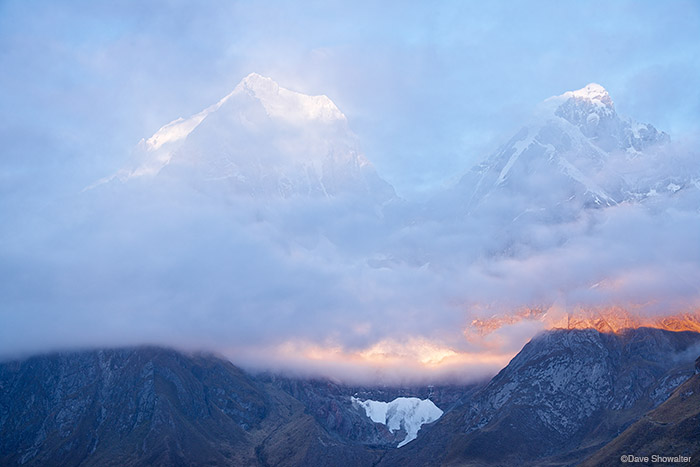 Early morning light breaks through layers of clouds to reveal Yerupaja (6634m) and Yerupaja Chico (6121m) from Carhuacocha...
