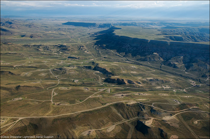The aerial perspective shows a fractured landscape and spiderweb of roads in the LaBarge Gas Field. This landscape has...