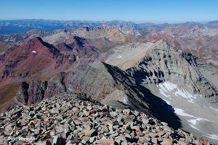 Endless ridges of multi-colored mountains in the elk range, looking across the south ridge of Castle Peak, 14,265'. Castle is...