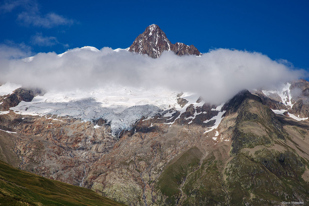 Below the Col De Seigne, Aiguille Des Glaciers is encircled by building clouds. Each afternoon on the Tour Du Mont Blanc these...