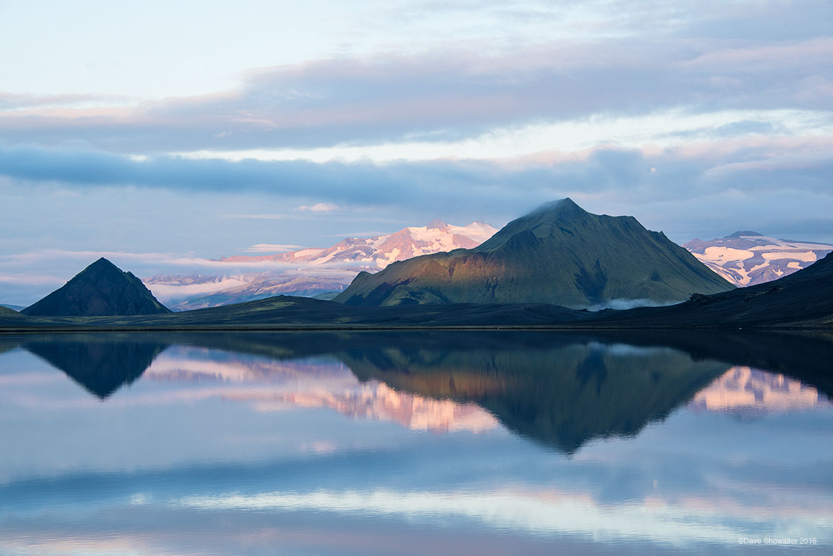 Volcanoes are reflected in early morning light along the shore of Alfvatn, a beautiful lake on the Landmannalaugar Trek.&nbsp...