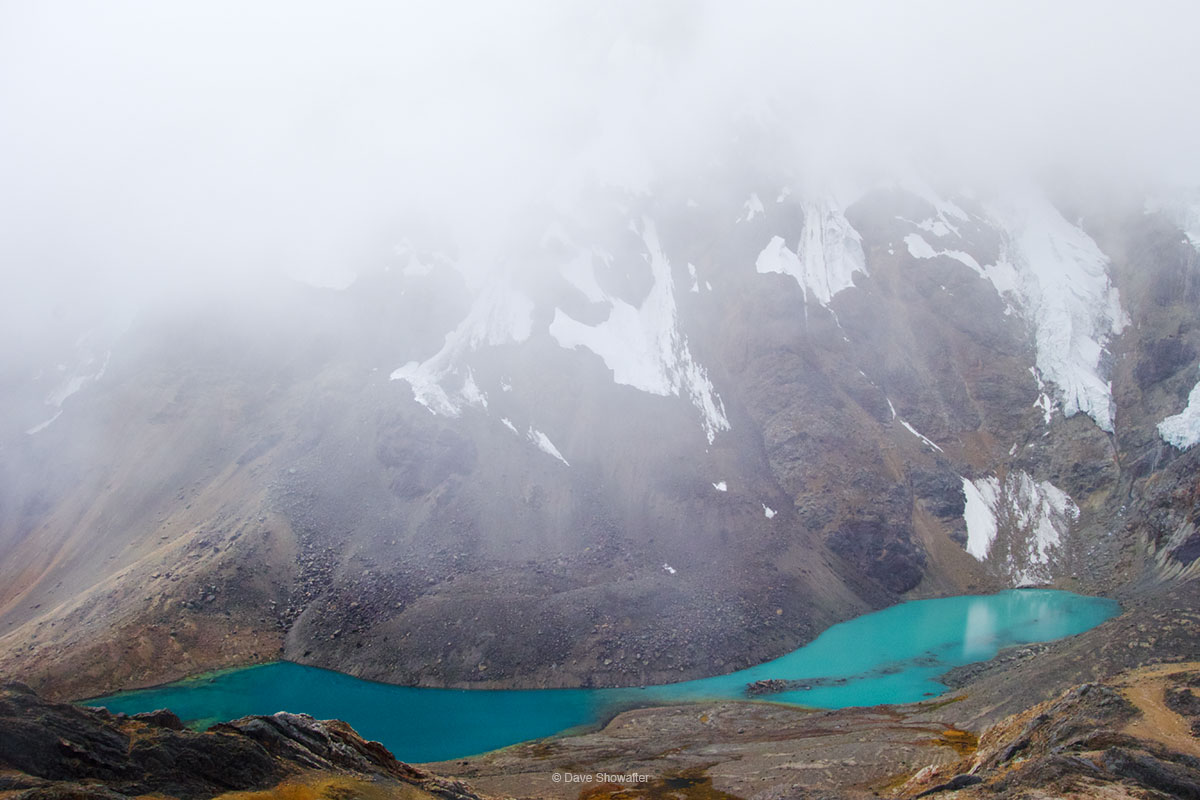 Laguna Huacrish's glacial blue waters contrast sharply with clouds draping West Huacrish Mountain (5622m). We were descending...
