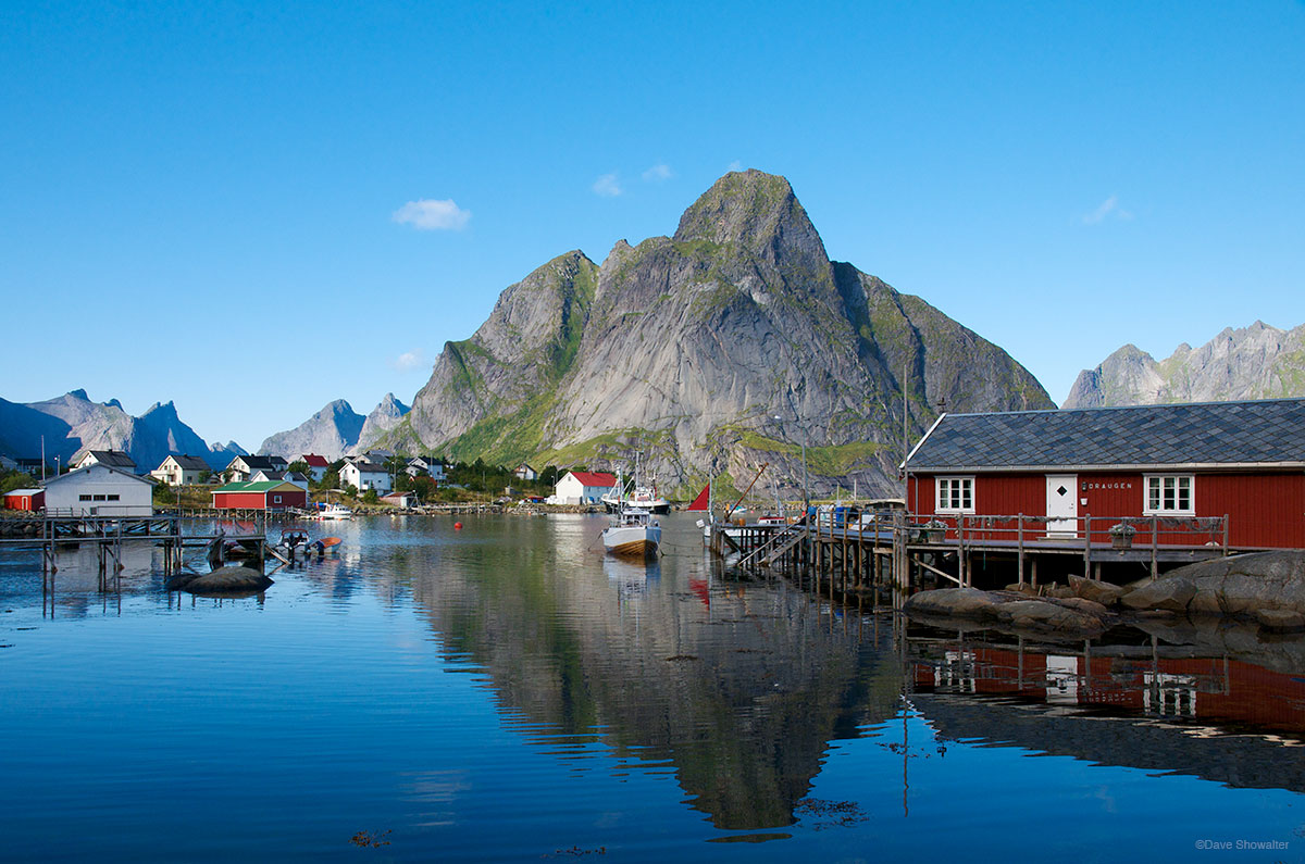 The rugged Lofoten mountainscape is reflected in the calm waters at Reine'. This fishing village is emblematic of the jaw...